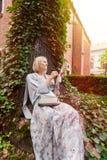 El inclinarse que se sienta hermoso de la mujer joven en un árbol en el medio de la hiedra Fotografía de archivo libre de regalías