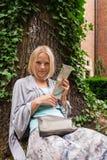 El inclinarse que se sienta hermoso de la mujer joven en un árbol en el medio de la hiedra Foto de archivo libre de regalías