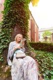 El inclinarse que se sienta hermoso de la mujer joven en un árbol en el medio de la hiedra Foto de archivo