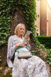 El inclinarse que se sienta hermoso de la mujer joven en un árbol en el medio de la hiedra Imagenes de archivo