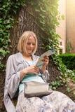 El inclinarse que se sienta hermoso de la mujer joven en un árbol en el medio de la hiedra Imagen de archivo libre de regalías