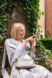 El inclinarse que se sienta hermoso de la mujer joven en un árbol en el medio de la hiedra Fotos de archivo