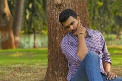 El inclinarse que se sienta y de pensamiento del individuo joven contra árbol imágenes de archivo libres de regalías