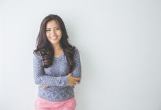 El inclinarse sonriente de la mujer casual en la pared blanca Imagenes de archivo