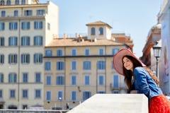 El inclinarse turístico de la mujer en la barandilla del puente en la calle soleada de la ciudad Fotografía de archivo