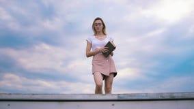 El inconformista bonito de la muchacha con un libro contra el cielo azul se sienta y lectura metrajes