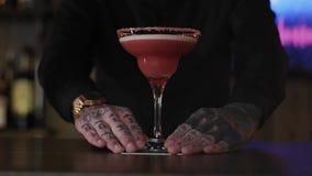 El inconformista del camarero preparó un cóctel alcohólico de la fresa exquisita en un vidrio almacen de video