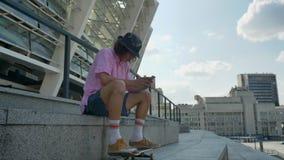 El inconformista del hombre joven está mecanografiando el mensaje en el smartphone, piernas en el monopatín, concepto urbano, con almacen de metraje de vídeo