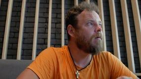 El inconformista del individuo con una barba come la pizza y da vuelta a su mirada a la cámara 4K v?deo 4K metrajes