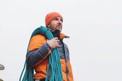 el Inconformista-escalador se retira en una chaqueta en una roca con una cuerda en su hombro foto de archivo