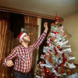 El inconformista extiende al top del árbol de navidad Fotografía de archivo