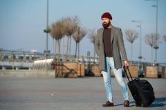 El inconformista listo disfruta de viaje Lleve el bolso del viaje Viaje de negocios Viaje barbudo del inconformista del hombre co foto de archivo