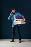 El inconformista masculino barbudo joven, vestido en camisa del dril de algodón, se coloca dentro que sostiene la caja de madera  fotografía de archivo libre de regalías