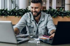 El inconformista sonriente del hombre de negocios trabaja simultáneamente en dos ordenadores portátiles, desarrolla el plan empre imagenes de archivo