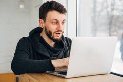 El inconformista sorprendido mira la pantalla del ordenador portátil fotografía de archivo