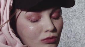 El inconformista tatuó la cara de la muchacha delante de trabajar el aparato de TV estático en sitio oscuro almacen de metraje de vídeo