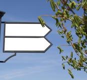 El indicador de dirección en el fondo del cielo azul con las inscripciones Imagen de archivo libre de regalías