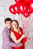 El individuo abraza a la muchacha con las bolas rojas Imagen de archivo