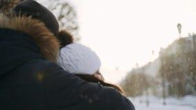 El individuo abraza a la muchacha Los copos de nieve que vuelan relucir en el sol Caminata del invierno almacen de metraje de vídeo
