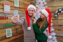 El individuo abraza a la muchacha y hace el selfie en el fondo del vestido encima de árbol Fotos de archivo libres de regalías