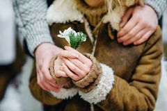 El individuo abraza a la muchacha y le da las flores foto de archivo