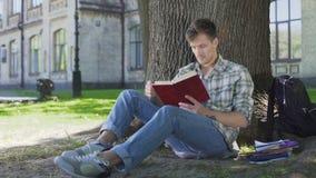 El individuo acaba el capítulo del libro de lectura, pensando en la historia que se sienta en la sombra del árbol almacen de video