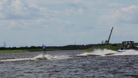 El individuo activo alegre monta waterski en el barco de motor de siguiente de la velocidad a lo largo del río metrajes