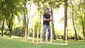 El individuo activo está jugando a un juego del lanzamiento del anillo en parque almacen de metraje de vídeo