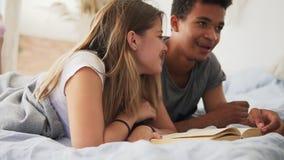 El individuo africano atractivo está leyendo un libro ruidosamente mientras que miente en cama así como su novia en casa en dormi almacen de video
