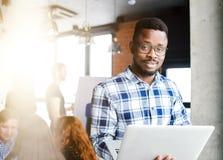 El individuo africano joven está probando el ordenador portátil fotografía de archivo