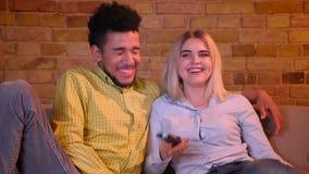 El individuo africano joven estrangula a su novia caucásica rubia que ve la TV en atmósfera casera acogedora almacen de metraje de vídeo