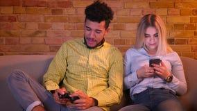 El individuo africano juega el videojuego con la palanca de mando atento y sus relojes bastante caucásicos de la novia en el telé almacen de metraje de vídeo