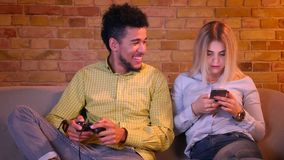 El individuo africano juega el videojuego con la palanca de mando y su novia caucásica rubia trabaja con smartphone en hogar acog almacen de video