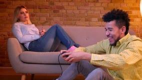 El individuo africano se sienta en el piso que juega el videojuego alegre y las esperas caucásicas de la muchacha que son agujere almacen de metraje de vídeo