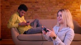 El individuo africano trabaja con smartphone en el sofá y la muchacha rubia caucásica que juegan el videojuego en piso con la pal almacen de metraje de vídeo