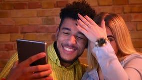 El individuo africano y la muchacha caucásica que tienen un vídeo invitan a la tableta que es alegre y que ríe feliz en casa almacen de video