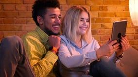 El individuo africano y la muchacha caucásica que tienen un vídeo invitan a la tableta que es linda y divertida en casa almacen de metraje de vídeo