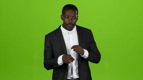 El individuo afroamericano baila en un traje de negocios, él tiene movimientos divertidos Pantalla verde metrajes