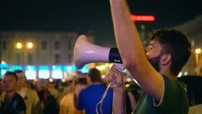 El individuo al megáfono en la camiseta verde de la ciudad de la noche ofrece apostar el partido de deporte almacen de video