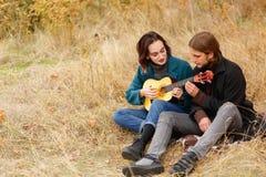 El individuo aprende jugar a la muchacha en la guitarra en un fondo del otoño Imagen de archivo