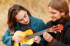 El individuo aprende jugar a la muchacha en la guitarra en un primer del fondo del otoño Foto de archivo libre de regalías