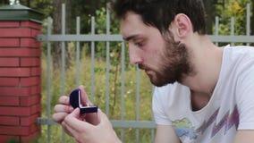 El individuo atractivo abre la pequeña caja azul del terciopelo con el anillo de bodas al lado de la cerca almacen de video