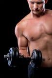 El individuo atractivo muscular coge una pesa de gimnasia foto de archivo