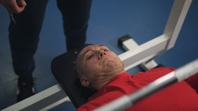 El individuo aumenta la barra de su hombre del pecho aumenta el peso libre bajo control del instructor en club de deportes metrajes