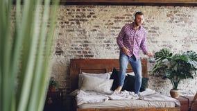 El individuo barbudo alegre en vaqueros y camisa está bailando en cama matrimonial y está cantando mientras que escucha la música almacen de metraje de vídeo