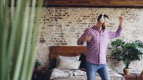 El individuo barbudo divertido se está divirtiendo, baile y está saltando con la guitarra mientras que escucha la música con los  metrajes