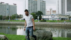 El individuo barbudo en vaqueros y camiseta azul está saltando de la roca almacen de metraje de vídeo