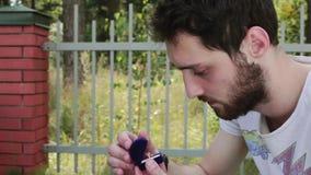 El individuo barbudo joven abre la pequeña caja azul del terciopelo con el anillo de bodas al lado de la cerca almacen de metraje de vídeo