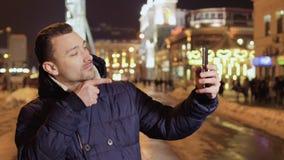 El individuo barbudo joven hace el selfie divertido en el fondo de la ciudad de la noche almacen de metraje de vídeo