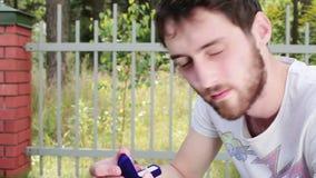 El individuo barbudo joven saca el anillo de bodas de la pequeña caja azul del terciopelo al lado de la cerca almacen de metraje de vídeo